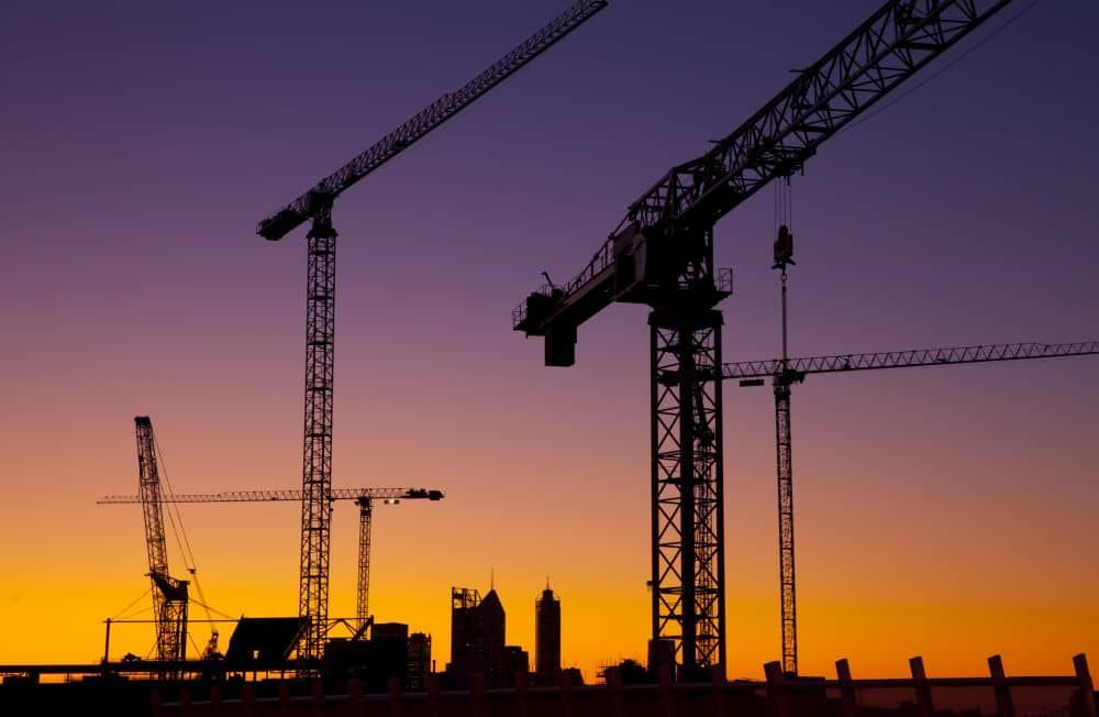 Silhouette of construction cranes with sunset on the background.
